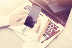 Mano femminile con un telefono cellulare in bianco e un computer portatile sulla tavola Immagine Stock