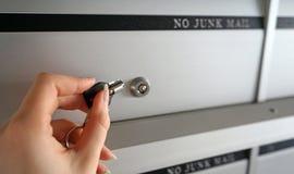 Mano femminile con una chiave Apertura della sua serratura della cassetta delle lettere per controllare i pacchetti fotografia stock