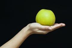Mano femminile con una mela verde Immagine Stock