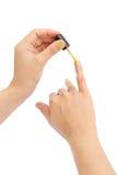Mano femminile con uno smalto dorato su fondo bianco Fotografie Stock Libere da Diritti