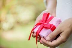 Mano femminile del fuoco selettivo che tiene un contenitore di regalo con il nastro rosso fotografia stock