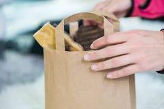 Mano femminile del raccolto che tiene il sacco di carta dal deposito immagini stock