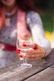 Mano femminile del ` s con i chiodi lunghi rossi che tengono un vetro di vino Immagine Stock Libera da Diritti