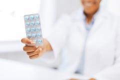 Mano femminile di medico che dà pacchetto delle pillole Fotografia Stock
