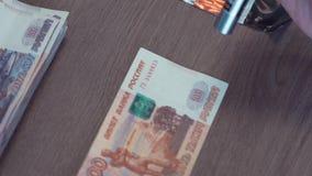Mano femminile facendo uso del laser per controllare cinque mila banconote della rublo sulla tavola video d archivio