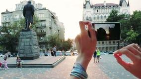 Mano femminile fotografata su una città storica dello Smart Phone durante il tramonto video d archivio
