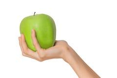 Mano femminile isolata della donna che tiene un verde Apple della frutta su un fondo bianco Fotografia Stock