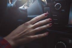 Mano femminile nell'automobile dietro la ruota immagine stock