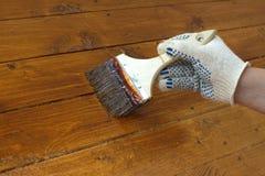 Mano femminile in pitture il pavimento di legno Foto del primo piano Fotografie Stock Libere da Diritti