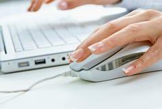Mano femminile usando il mouse del calcolatore Fotografia Stock Libera da Diritti