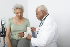 Mano fracturada del doctor Checking Patient Fotos de archivo
