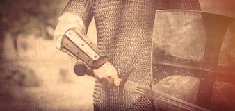 Mano fuerte del caballero con la espada y el escudo hermosos en el centro fotos de archivo libres de regalías