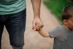 Mano fuerte del padre que lleva a cabo una pequeña mano de su hijo Fotografía de archivo