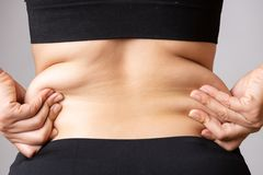 Mano grassa della donna che tiene l'eccessivo grasso della pancia Sanità e concetto di stile di vita di dieta della donna per rid fotografia stock libera da diritti