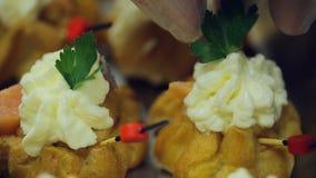 Mano in guanto eliminabile decorato con i panini della crema del prezzemolo all'archivio al banchetto stock footage