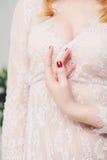 Mano hermosa del ` s de la novia en la bata de casa blanca boda juventud pureza fotos de archivo