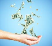 Mano humana con el dinero y monedas que caen en el fondo azul imagenes de archivo