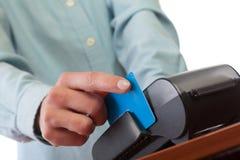 Mano humana con el golpe fuerte de la tarjeta de crédito a través del terminal para la venta Imagen de archivo libre de regalías