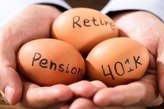 Mano humana con el huevo que muestra el texto de la pensión y del retiro foto de archivo