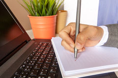 Mano humana con la escritura de la pluma en el cuaderno que alinea encima imagen de archivo