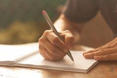 Mano humana con la escritura de la pluma en el cuaderno que alinea encima Fotografía de archivo