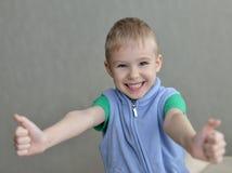 Mano humana del niño que gesticula el pulgar encima de la muestra del éxito Foto de archivo libre de regalías