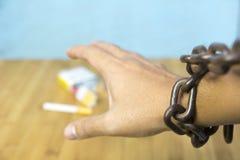 Mano humana encadenada que intenta coger el cigarrillo en la tabla imágenes de archivo libres de regalías