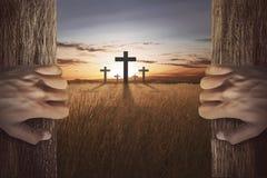 Mano humana que abre la puerta de madera y que mira la cruz Imagenes de archivo