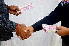 Mano humana que da moneda india el uno al otro imagen de archivo