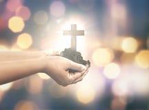 Mano humana que lleva a cabo la cruz cristiana con el suelo en la mano Imagen de archivo