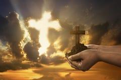 Mano humana que lleva a cabo la cruz cristiana con el suelo en la mano Imagen de archivo libre de regalías