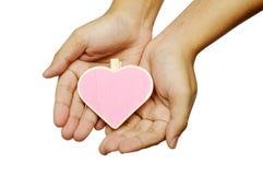 Mano humana que lleva a cabo la muestra de madera de la forma del corazón imágenes de archivo libres de regalías