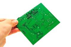Mano humana que lleva a cabo la tarjeta de circuitos verde de ordenador Fotografía de archivo