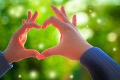 Mano humana que muestra la muestra del amor del gesto en la naturaleza verde fresca fotos de archivo