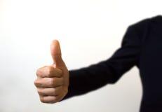 Mano humana que muestra los pulgares para arriba en el primero plano blanco Foto de archivo libre de regalías