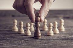 Mano humana que pone el pedazo de ajedrez del rey Imagen de archivo