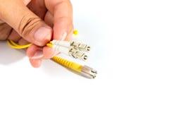 Mano humana que sostiene el cordón de remiendo de la fibra óptica Imagen de archivo