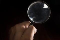 Mano humana que sostiene la lupa Foto de archivo libre de regalías