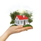 Mano humana que sostiene la pequeña casa con los árboles y stock de ilustración