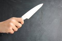 Mano humana que sostiene un cuchillo en la pizarra Fotografía de archivo