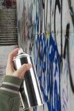 Mano humana que sostiene una poder de espray de la pintada Foto de archivo