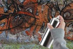 Mano humana que sostiene una poder de espray de la pintada Imagenes de archivo