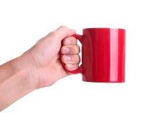 Mano isolata che tiene tazza rossa Fotografia Stock