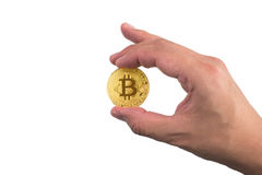 Mano isolata che tiene un bitcoin dorato con la punta del dito su bianco Fotografie Stock Libere da Diritti