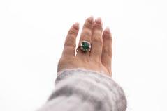 Mano izquierda con el anillo de compromiso esmeralda imagenes de archivo