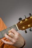 Mano izquierda de los jugadores de la guitarra acústica Imagen de archivo libre de regalías