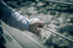 Mano joven del muchacho que sostiene la cerca de alambre de metal Fotos de archivo