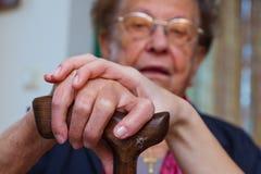 Mano joven y vieja con un bastón que recorre Imágenes de archivo libres de regalías