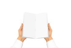 Mano in manica bianca della camicia che tiene il libretto in bianco dell'opuscolo in Fotografia Stock