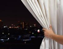 Mano maschio aperta la tenda di finestra e vedere i precedenti della città di notte fotografie stock libere da diritti